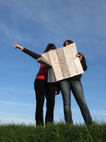 2 women reading a map and pointing in the direction to head.