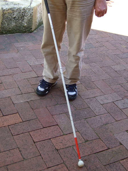 Blind man using a white cane with a red tip.